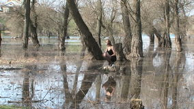 Pretty Model Posing At Stump In Park  In Flood. Zoom in: young pretty model in short black dress and shoes with dark hair shoulder length is sitting on hunkers stock video
