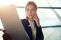 Pretty model reading contract and and consult with a lawyer. Portrait of young lovely business woman having cell phone conversation while examining paperwork in stock photography