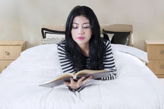 Pretty model reads a book on bedroom Royalty Free Stock Photo