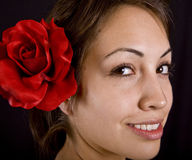 Pretty model with red flower in her hair. A pretty hispanic model with a red flower in her hair Stock Images