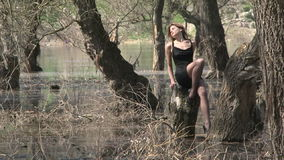 Pretty Model In Sexy Pose On Stump At Park In. This is a footage of a young pretty model in short black dress and shoes with dark hair shoulder length sitting on stock footage
