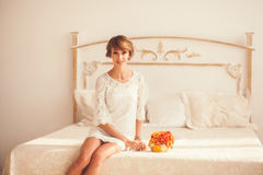 Pretty model sitting on the bed in the bedroom Royalty Free Stock Photography