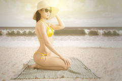 Pretty model sitting at seashore Stock Image