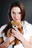 Pretty model with toy bear. Pretty model with brown toy bear in her hands Royalty Free Stock Images