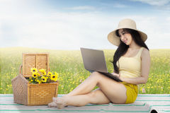 Pretty model uses laptop on meadow Royalty Free Stock Photo