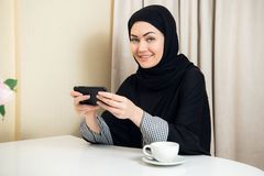 Pretty modern Arabic woman playing on smart phone at home stock image