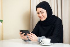Pretty modern Arabic woman playing on smart phone at home royalty free stock photo