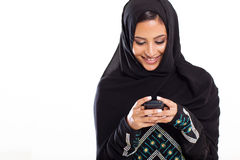 Arabic woman phone. Pretty modern Arabic woman playing on smart phone isolated on white Stock Photos