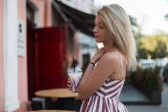 Pretty modern beautiful young blond woman in a stylish pink striped dress with a sweet cold milk drink walk on the street. Near a open cafe. Cute girl model stock photo