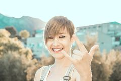 Pretty, modern girl making a rocking gesture. Woman making horns with her hand stock photos