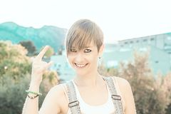 Pretty, modern girl making a rocking gesture. Woman making horns with her hand stock photography