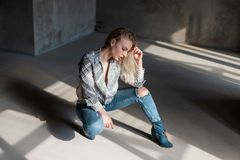 Pretty modern young woman blonde in stylish summer shirt in blue ripped jeans in trendy cowboy boots posing sitting indoors. With sunlight. American beautiful royalty free stock image