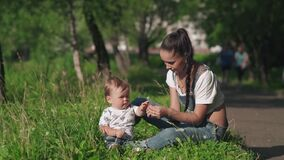 Pretty tender mommy and her little son sitting on the grass in the picturesque park . Beautiful young mother giving a