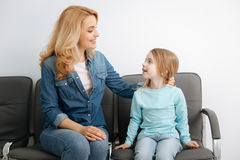 Pretty mom sitting in the hall with her daughter Stock Photography