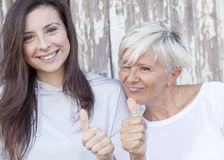 Pretty mother and adult daughter make the sign royalty free stock photography