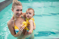 Pretty mother and baby at the swimming pool. At the leisure center royalty free stock image