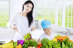 Pretty mother and boy prepare salad. Photo of a pretty young mother and little boy prepare vegetables salad for lunch in the kitchen at home Royalty Free Stock Images