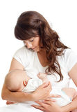 Pretty mother breast feeding her infant. Young mother breast feeding her infant over white background Stock Photos