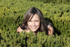 Pretty mother crouching in bushes. Pretty smiling mother crouching in green bushes Stock Photo