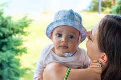 Pretty mother cuddle cute blue eyed baby in hat, infant face portrait stock image