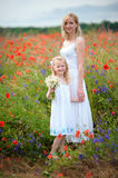 Pretty mother with cute young daughter on a poppy field with whi Royalty Free Stock Photos