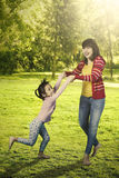 Pretty mother and daughter playing at park Stock Photography