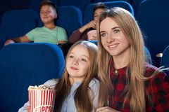 Pretty mother and daughter watching film in cinema. stock images