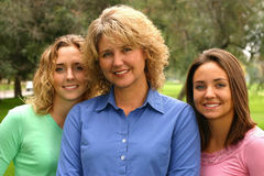 Pretty mother with daughters. A beautiful woman stands outdoors with her pretty daughters stock images