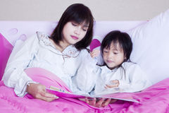 Pretty mother and girl read book on bed. Portrait of young mother and her daughter reading a storybook together in the bedroom Stock Photo