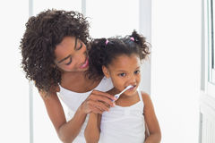 Pretty mother helping her daughter brush her teeth Royalty Free Stock Photos