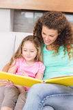 Pretty mother helping her little daughter read a storybook Stock Photography