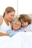 Pretty mother and her children reading book. Lying in bed Stock Image