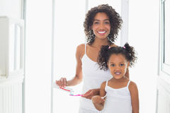 Pretty mother with her daughter brushing their teeth Royalty Free Stock Image
