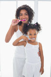 Pretty mother with her daughter brushing their teeth Stock Photos
