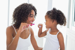 Pretty mother with her daughter brushing their teeth Royalty Free Stock Photos