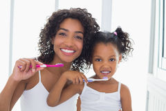 Pretty mother with her daughter brushing their teeth Royalty Free Stock Images