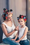 Pretty mother and her daughter having fun with lipstick while do Royalty Free Stock Photography