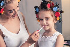 Pretty mother and her daughter having fun with lipstick while do Royalty Free Stock Photo