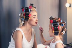 Pretty mother and her daughter having fun with lipstick while Royalty Free Stock Image