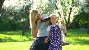 Pretty mother and her daughter on swing in blooming spring park. Static shot stock video