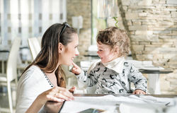 Pretty mother with her little daughter sitting in the restaurant Stock Images