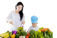 Pretty mother with her son making a salad. Image of pretty mother standing in the studio while making a salad with her son Royalty Free Stock Images