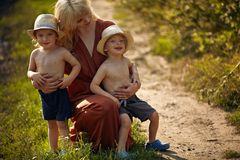 Pretty mother hugging her beloved sons stock photo