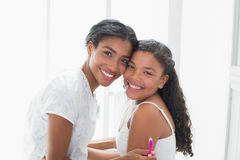 Pretty mother hugging her daughter smiling at came Royalty Free Stock Photo