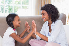 Pretty mother playing clapping game with daughter on couch Stock Images