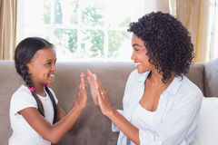 Pretty mother playing clapping game with daughter on couch Royalty Free Stock Images