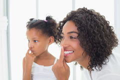 Pretty mother putting face cream on with her daughter Royalty Free Stock Image