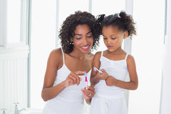 Pretty mother showing her daughter her toothbrush Royalty Free Stock Photos
