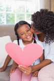 Pretty mother sitting on couch with daughter reading heart card Stock Photography