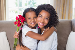 Pretty mother sitting on the couch with her daughter holding roses Stock Photo